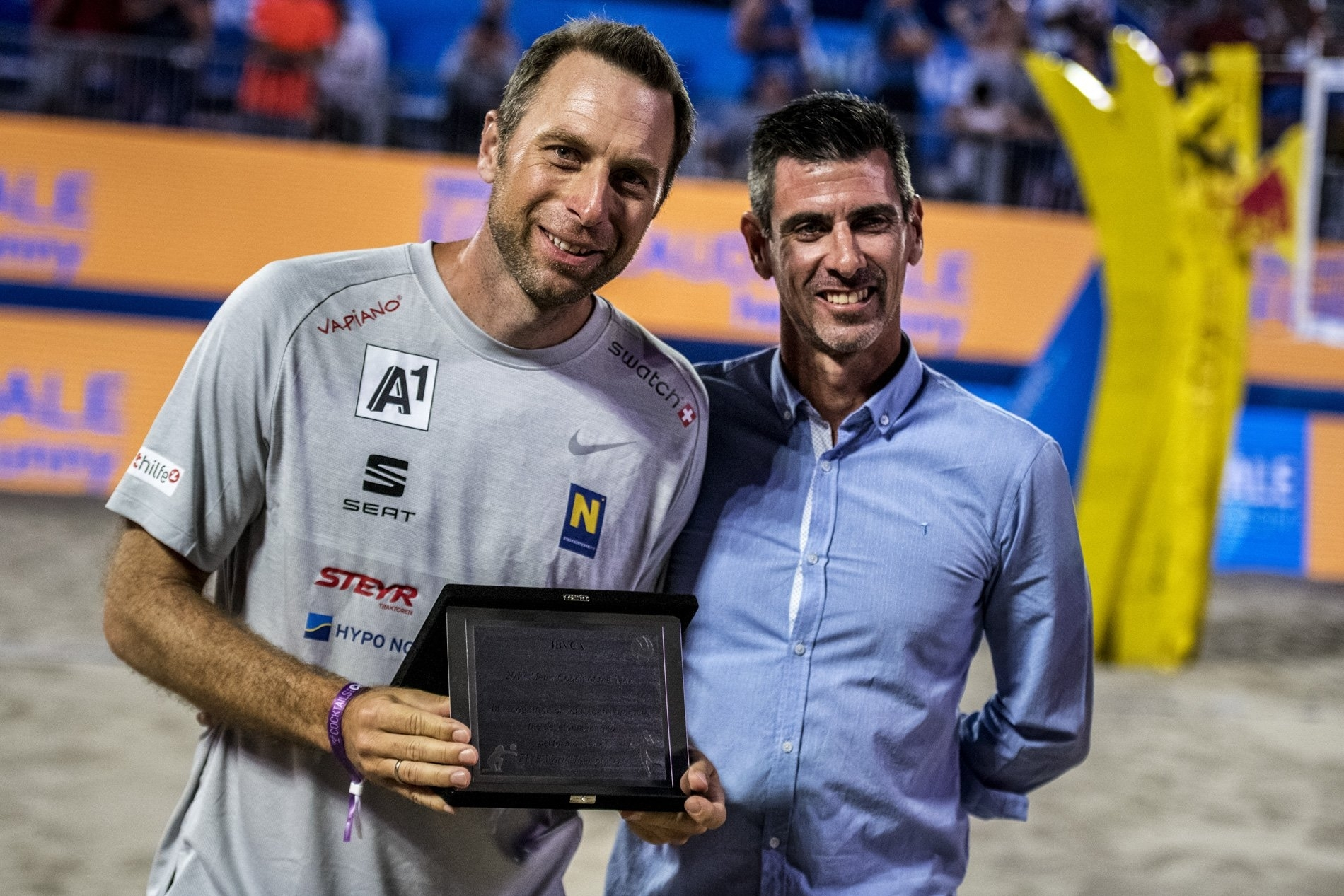 Robert Nowotny (left) receives his awarded on the Red Bull Beach Arena sand